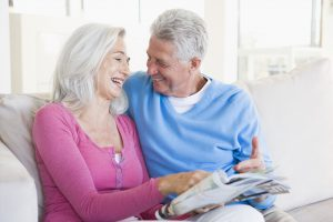 Elderly Caucasian Couple Laughing on the Couch while Reading a Magazine