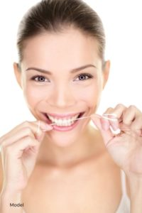 Young Woman Happily Flossing Teeth