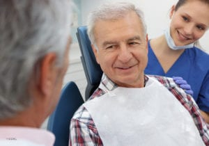Mature Male In Plaid Shirt Sitting In Dental Chair Talking To Doctor With Assistant Smiling
