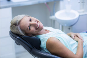 Older Woman Smiling and Laying on Examination Chair