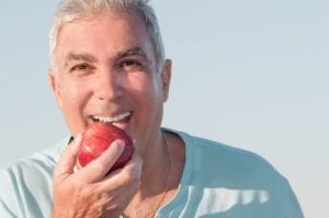 Mature Man With Sky Blue Shirt Eating Red Apple Outdoors