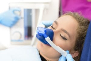 Patient Under Sedation With Breathing Mask Sleeping on Dental Chair