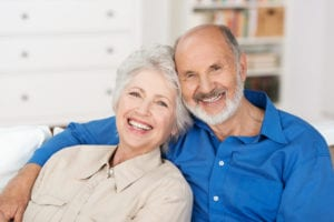 Older Couple Smiling Sitting On Couch At Home