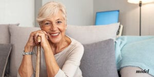 Female with Dental Implants Sitting on Couch
