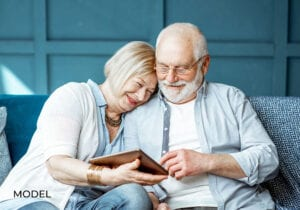Old Man and Woman Researching Dental Implant Failure on Tablet