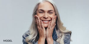 Older Female Patient With Emergency Dental Implants Holding Face with Hands