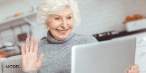 Older Female Reading About Emergency Dental Implant Qualifications